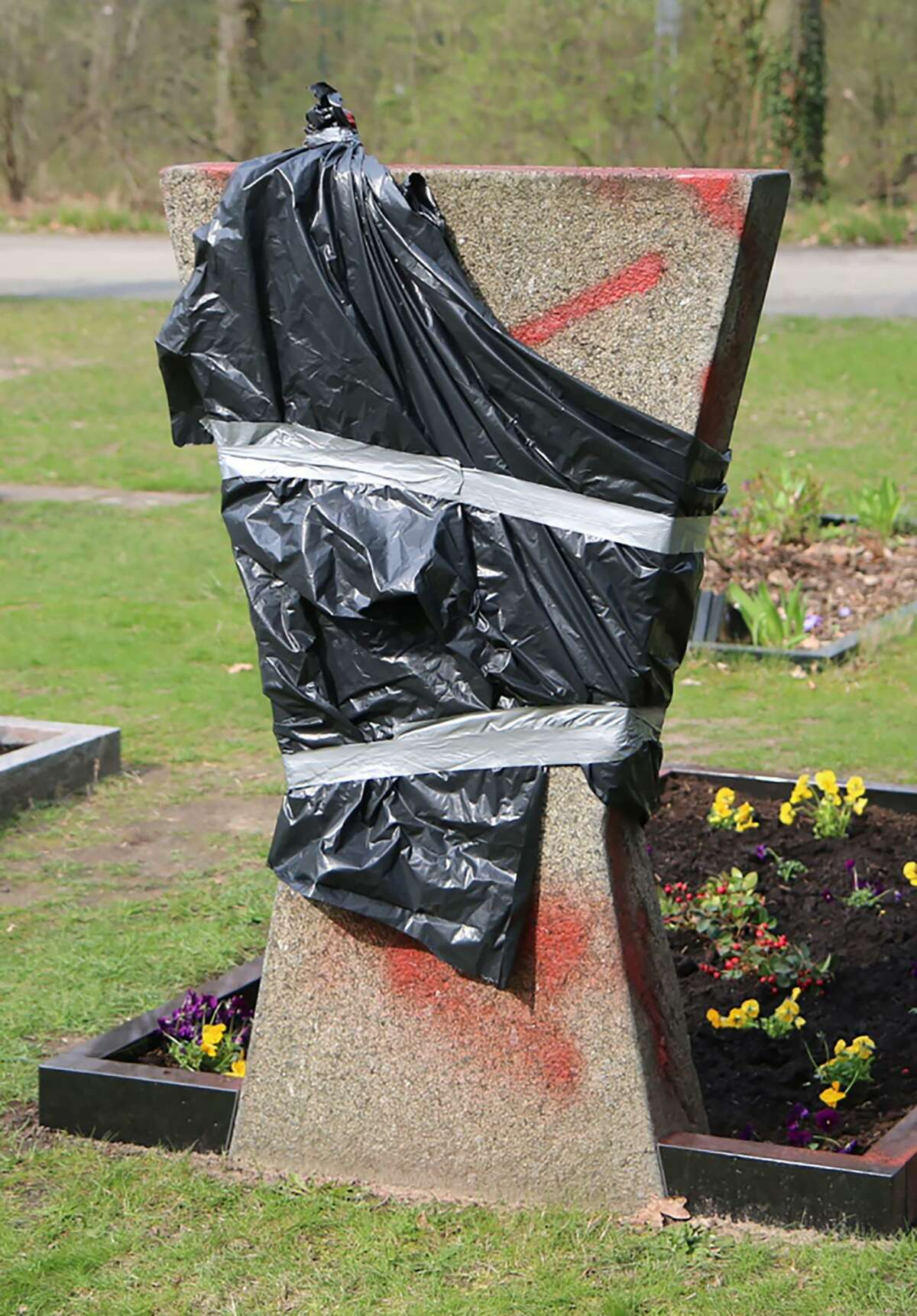 A gravestone covered with foil is pictured on the park cemetery Neukoelln in Berlin on April 3. Unidentified people smeared with swastikas the tombstones of two policemen killed in service on April 3 in Berlin, the police said.