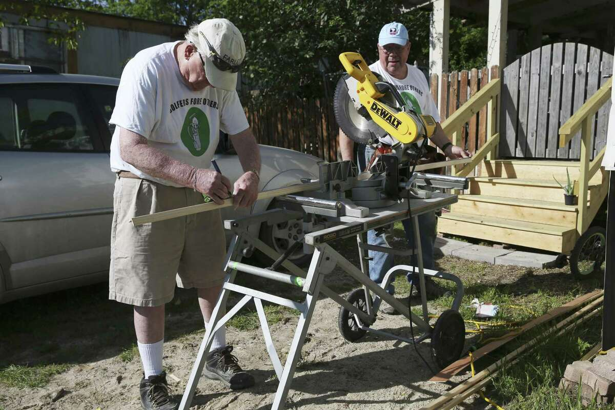 Golfers Fore Others volunteers Mike McClelland, left, and Rev. Ed Brogan cut wood outside a mobile home in the Shady Rest mobile home park. As the name suggests, most GFO volunteers are avid golfers, so they confine their good work to Mondays because that's when golf courses close for maintenance.