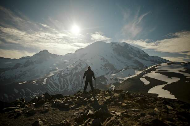 A hiker stands on Burroughs Mountain while the Moon rises over Mount Ranier.