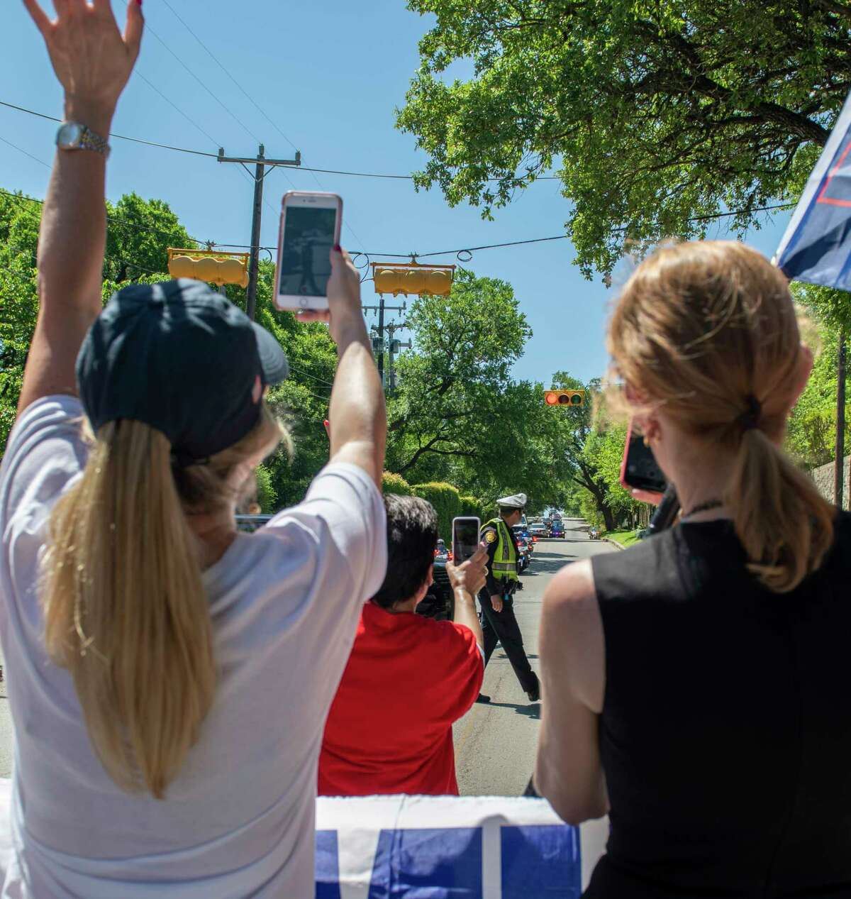 Trump supporters wave at President Donald Tump's motorcade on route to a fundraiser at Alamo Heights on Wednesday, April 10, 2019.