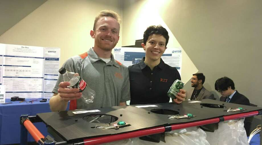 Patrick Finnerty and Catherine Krawiec, students at the Rochester Institute of Technology, display their bottle and container return project, which uses a light beam counter to increase the efficiency and output of a Mount Morris-based recycling facility. The duo was part of five-person team that won second-place and $10,000 in the event.  Photo: Diego Mendoza-Moyers