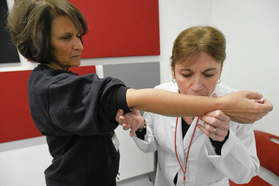 Karen Giachino conducts a sniffing test on Nancy Colletto, of Stamford, as she participates in a fragrance-testing study at Henkel's research-and-development center at 200 Elm St. in downtown Stamford. Photo: Matthew Brown / Hearst Connecticut Media / Stamford Advocate