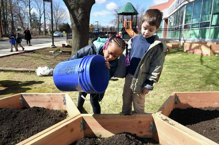 Khloe Hill, left, and James Mardis dump a bucket of dirt into a raised-bed garden box in front of Beecher School in New Haven as part of Outdoor Day organized by Connecticut Schoolyards program manager Suzannah Holsenback on April 10, 2019. Photo: Arnold Gold / Hearst Connecticut Media / New Haven Register