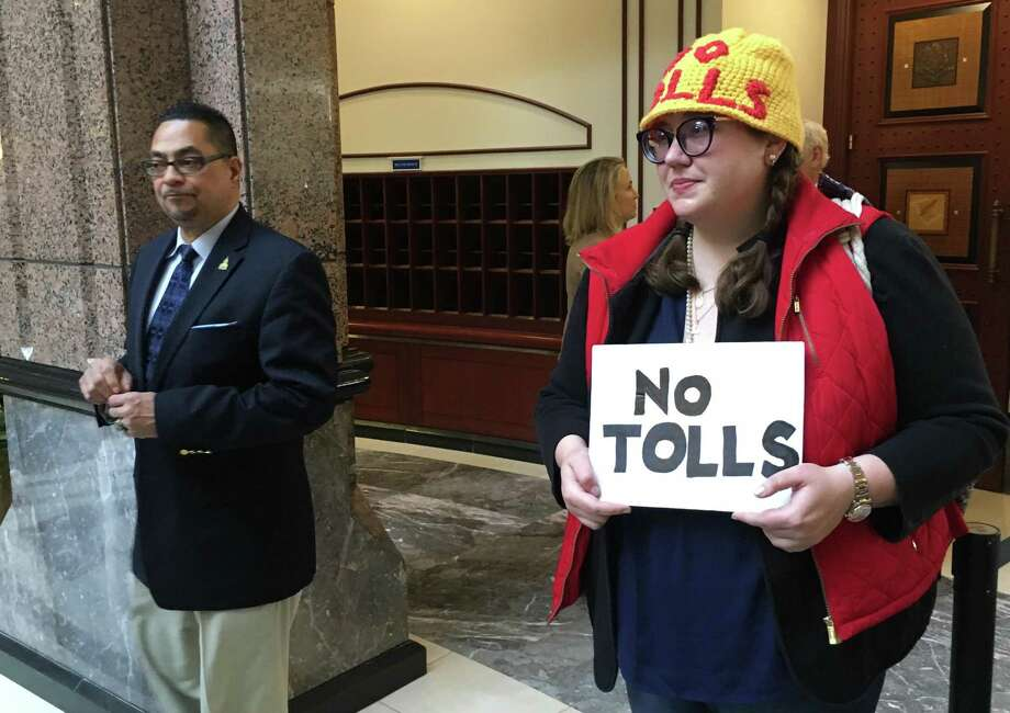People who oppose Gov. Ned Lamont's tolls proposal for Connecticut's highways wears a handmade hat out front of the state Capitol. At left is Rep. Gerry Reyes, D-Waterbury. Photo: Dan Haar / Hearst Connecticut Media