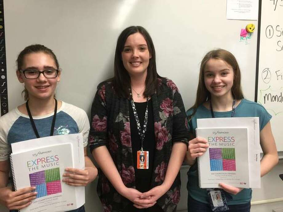St. Louis Symphony Orchestra's Express the Music finalists Katie Weems and Sara Davis from Lincoln Middle School, with their teacher Cynthia Hoxsey. Both girls were presented with books containing the published works of all 75 finalists.