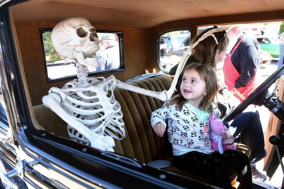 Helaina Kidder, 3, of Orange looks at a skeleton sitting in the passenger seat of a 1931 Ford Coupe after getting a chance to sit behind the steering wheel with her mother, Debra, at the annual Dust-Off Car Cruise at Heav'nly Donuts in Derby to benefit Spooner House in 2017. The car is owned by Rick George of Milford. Photo: Hearst Connecticut Media File