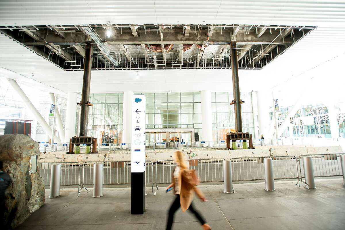 A pedestrian passes temporary support columns holding the Transbay Transit Center as work continues to repair cracked steel support girders on Wednesday, April 10, 2019, in San Francisco.