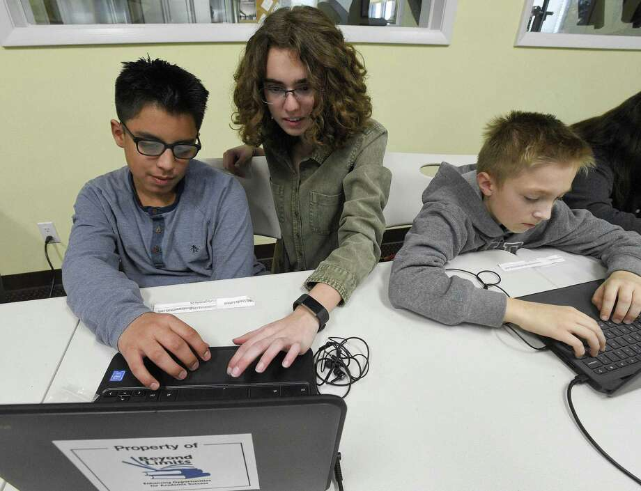 Sydney Eben, a student volunteer from Westhill High School, works with Adiel Crosby during a computer science class on Thursday in Stamford. Beyond Limits Academic Program, a program in Stamford offers free computer science classes to middle school students. During the eight-week class, 16 middle school boys and girls from sixth through eighth grades an introduction to Python, an entry point to learn a versatile, professional-level coding language. Photo: Matthew Brown / Hearst Connecticut Media / Stamford Advocate