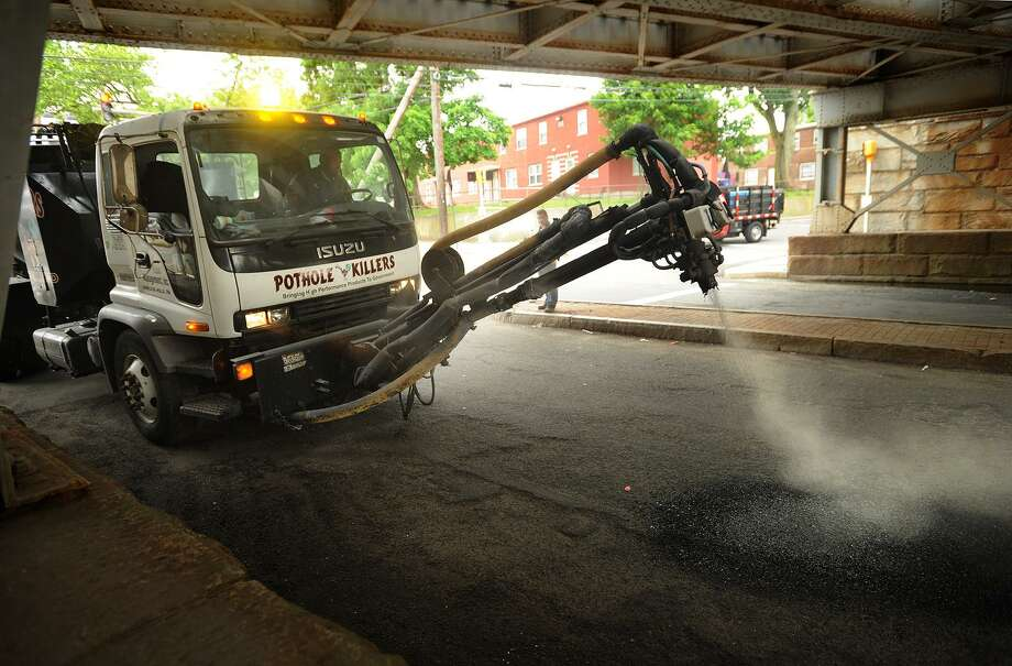 """A file photo of """"The Pothole Killer,"""" a pothole repair vehicle being leased by the city of Bridgeport, fills a pothole beneath the Park Avenue train overpass in Bridgeport, Conn., on Wednesday, June 11, 2014. Photo: Brian A. Pounds / Brian A. Pounds / Connecticut Post"""