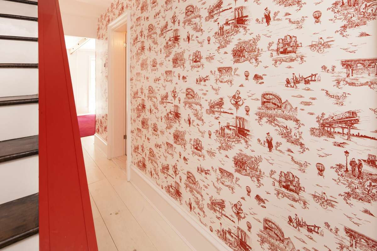 An image of the Brooklyn Toile wallpaper, which served as the inspiration for the Bay Area Toile. The wallpaper features imagery of Brooklyn in a French country toile style and was made in collaboration between Beastie Boys' Mike D, Revolver New York and Flavor Paper. Here, the wallpaper is seen in the hallway of Mike D's former Brooklyn home. The imagery includes Biggie, Coney Island, Borough Hall Station and others.