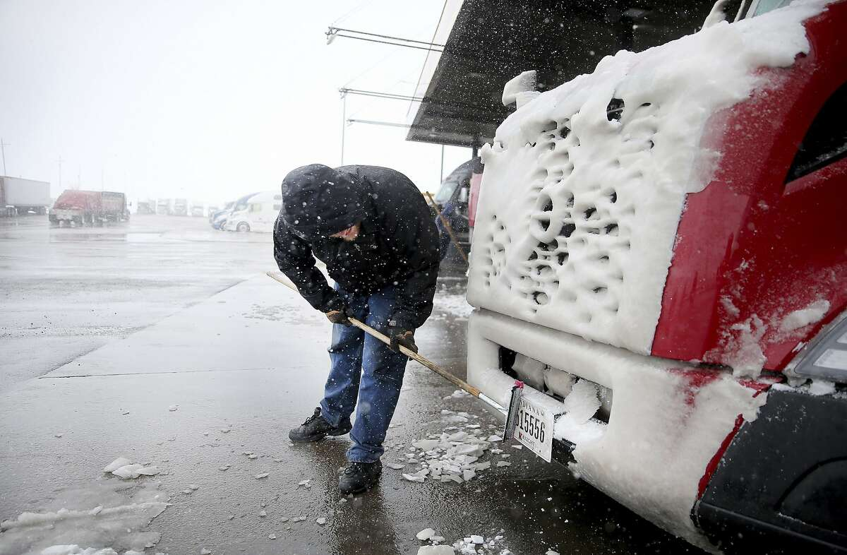 Alan Brown of Colorado Springs, Colo., attempts to clear ice from his truck's license plate as he prepares to continue the trek to Billings, Mont., while passing through Love's Travel Stop during a blizzard warning hitting southeast Wyoming Wednesday, April 10, 2019, in Cheyenne. People in Colorado and Wyoming were urged to get home early Wednesday and stay there before snow and wind from a powerful spring storm make travel all but impossible.(Jacob Byk/The Wyoming Tribune Eagle via AP)