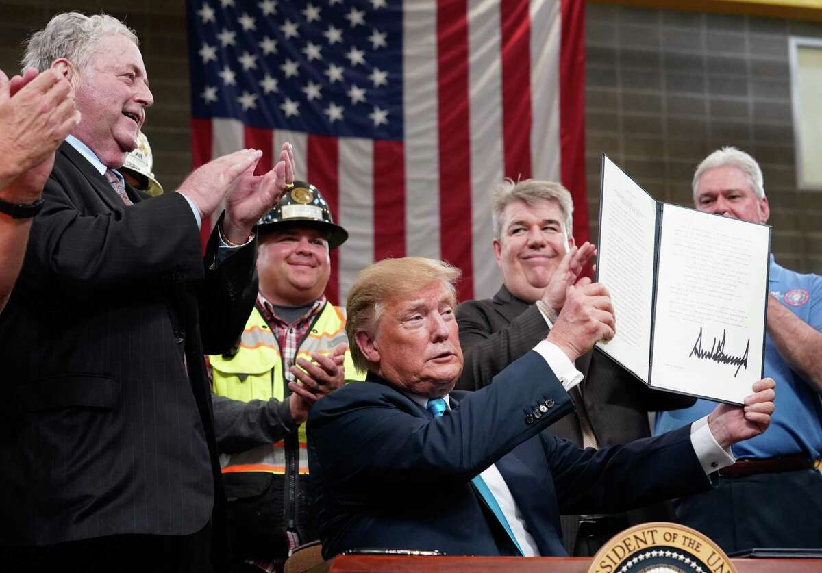 President Donald Trump displays one of two executive orders he signed at the International Union of Operating Engineers (IUOE) International Training Center, Wednesday, April 10, 2019 in Crosby.