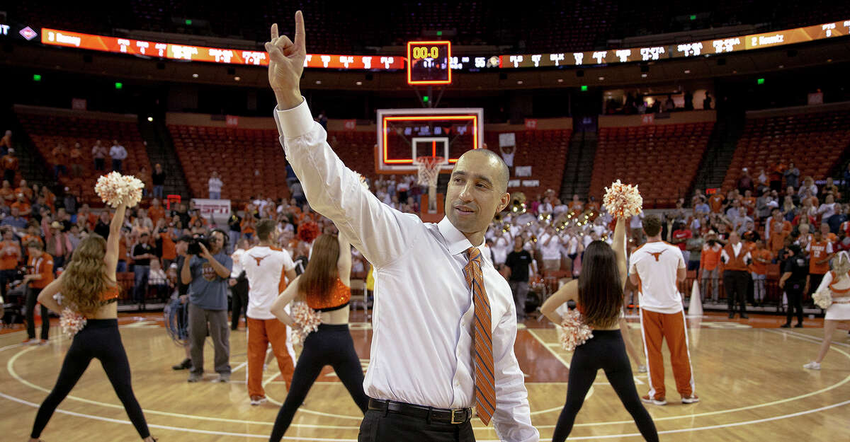 """Texas coach Shaka Smart holds up the """"Hook 'em Horns"""" sign following Texas' 68-55 win over Colorado the quarterfinals of the NIT on March 27, 2019, in Austin.)"""