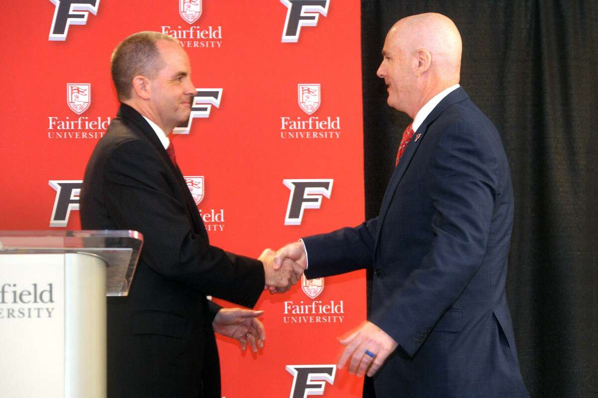 Fairfield University Athletic Director Paul Schlickmann sits welcomes new men's basketball coach Jay Young at a press conference on the Fairfield, Conn. campus April 10, 2019.
