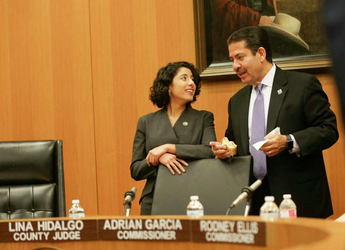 Newly-elected Harris County Judge Lina Hidalgo laughs with Commissioner Adrian Garcia during her first Harris County Commissioners Court meeting since being elected on Tuesday, January 8, 2019 in Houston.