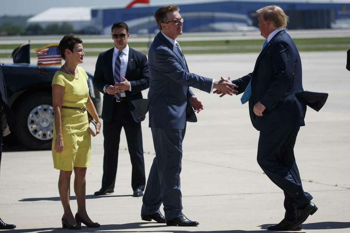 Texas State Senator Donna Campbell, left, watches as Lt. Gov. Dan Patrick, R-Texas, greets President Donald Trump as he arrives at San Antonio International Airport, Wednesday, April 10, 2019, in San Antonio. (AP Photo/Evan Vucci)