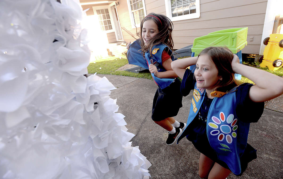 Renee VanPoeck (left) and Juliet Mikkelsen celebrate as they get a paper flower to stick as they and members of Girl Scout Troop 130363 work on final float preparations for this Friday's Neches River Festival parade in downtown Beaumont. The theme of their float this year is