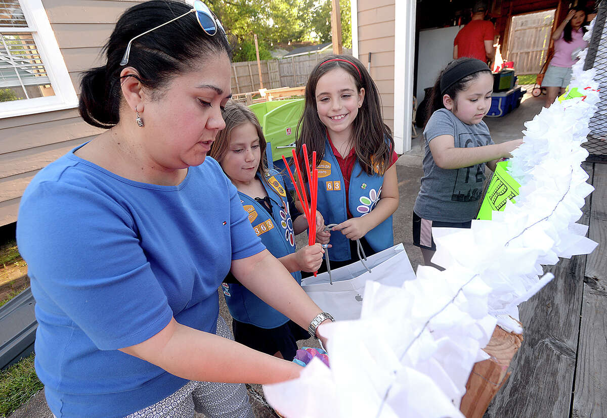 From left, Juanita Sanchez, Juliet Mikkelsen, Renee VanPoeck and Sophia Gutierrez with Girl Scout Troop 130363 work on final float preparations for this Friday's Neches River Festival parade in downtown Beaumont. The theme of their float this year is
