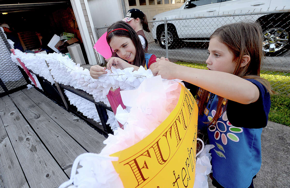 Renee VanPoeck (left) and Juliet Mikkelsen with Girl Scout Troop 130363 work on final float preparations for this Friday's Neches River Festival parade in downtown Beaumont. The theme of their float this year is