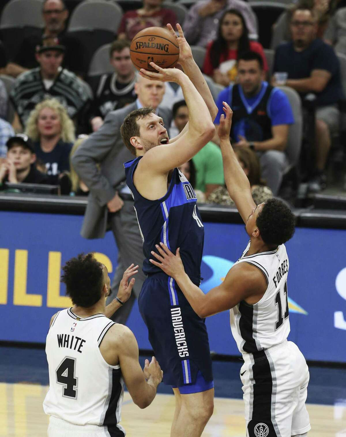 Dallas Mavericks' Dirk Nowitzki (41) shoots and makes his first basket against Spurs' Bryn Forbes (11) and Derrick White (04) in the first quarter at the AT&T Center on Wednesday, Apr. 10, 2019. (Kin Man Hui/San Antonio Express-News)