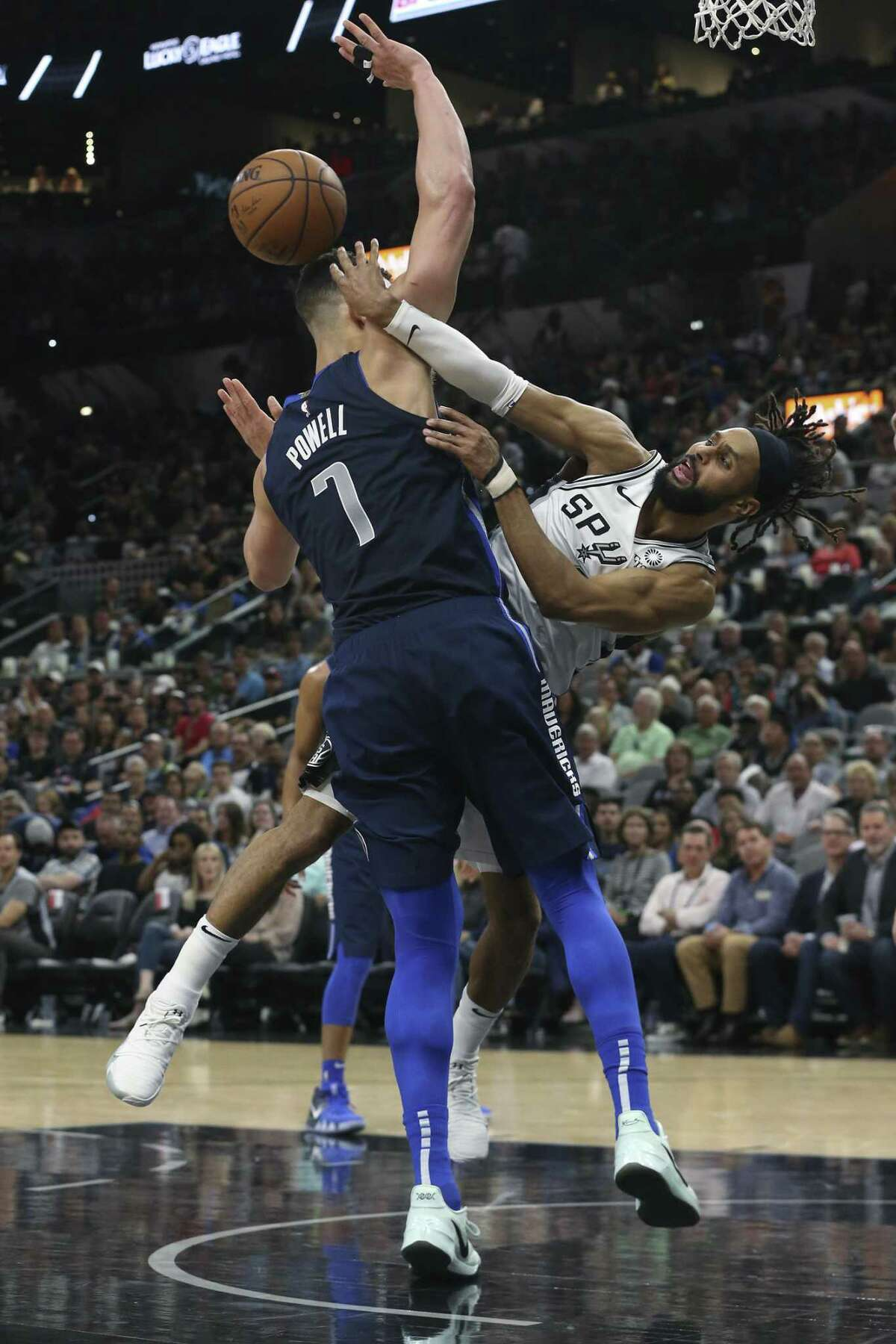 Dallas Mavericks' Dwight Powell trips San Antonio Spurs' Patty Mills as he passes the ball during the first half at the AT&T Center, Wednesday, April 10, 2019.