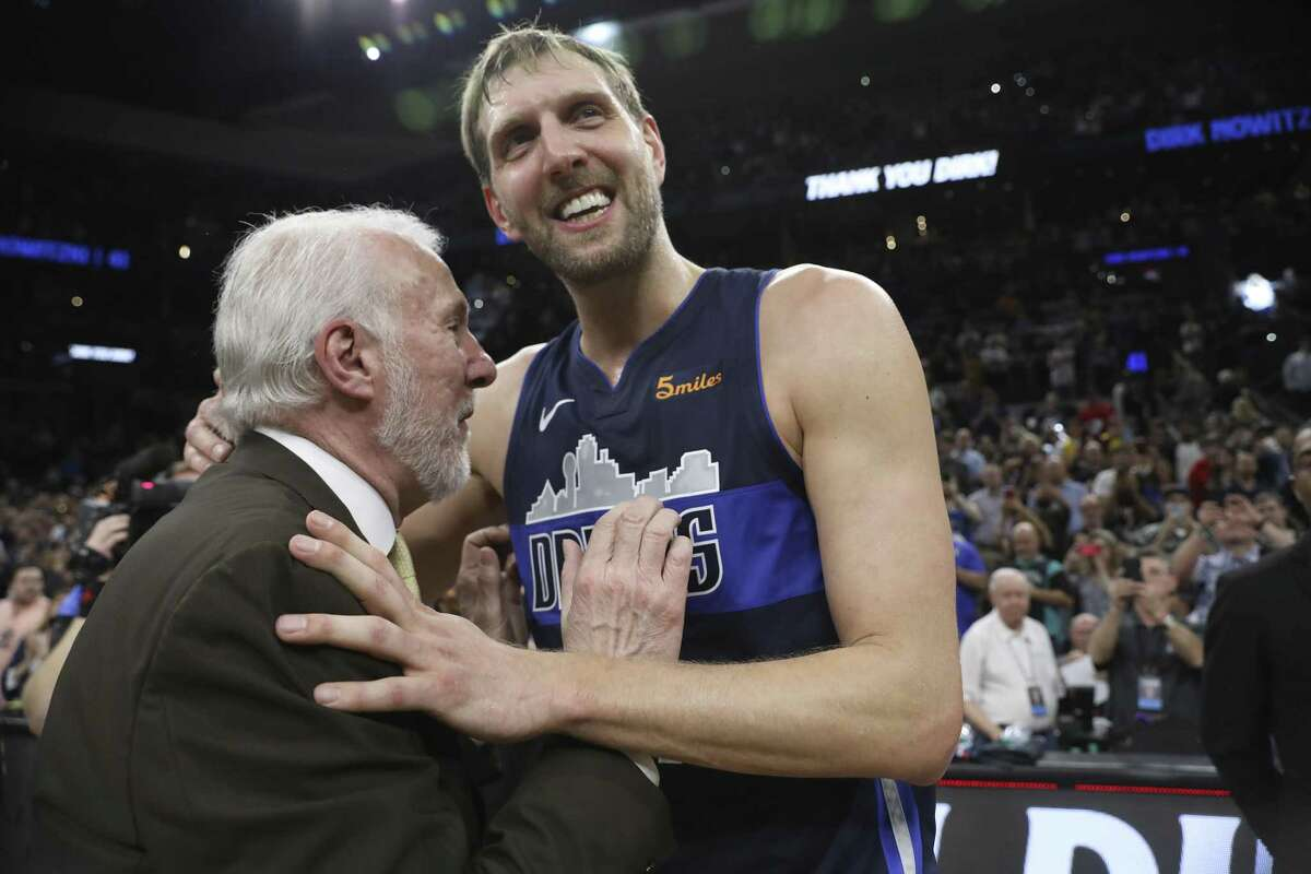 Dallas Mavericks' Dirk Nowitzki speaks with San Antonio Spurs' head coach Gregg Popovich at the end of his last career game at the AT&T Center, Wednesday, April 10, 2019. The Spurs won, 105-94.
