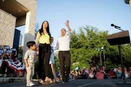 """Democratic Presidential hopeful Julian Castro walks onstage alongside his wife Erica Lira Castro and children Cristian Castro, left, and Carina Castro, right, during his """"People First Rally"""" at Hemisfair Park in downtown San Antonio, Texas on Wednesday, April 10, 2019."""