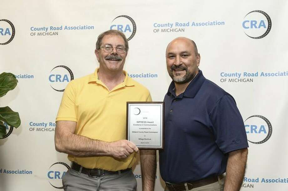 Midland County Road Commission Managing Director Terry Palmer, left, and SuperintendentSam SanMiguel pose with the IMPRESS Award that MCRCwon at the CRA Highway Conference. (Photo provided)