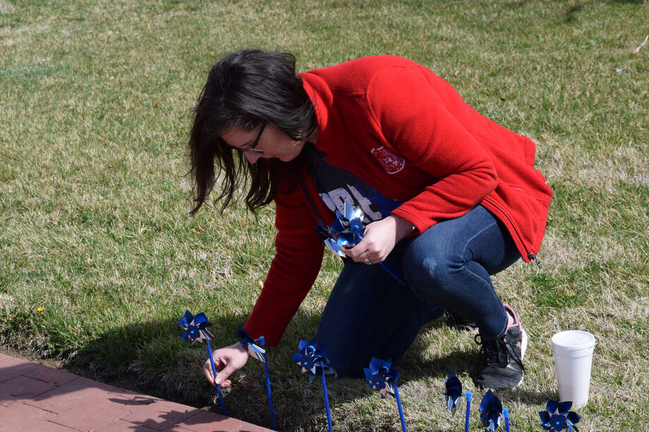 A volunteer places blue pinwheels along the walkways at a downtown park. Photo: Ellysa Harris/Plainview Herald