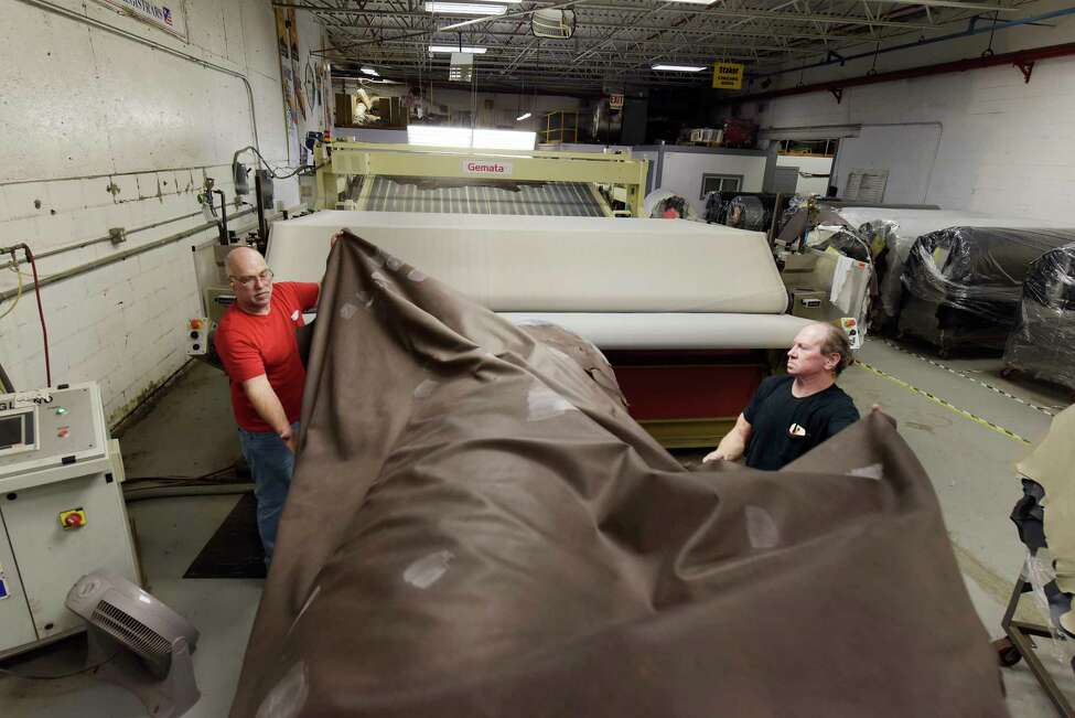 Employees, Oakley Cole, left, and Bill Mouck pull a large piece of leather to feed it into a machine that will soften the material at Townsend Leather on Monday, March 5, 2018, in Johnstown, N.Y. (Paul Buckowski/Times Union)