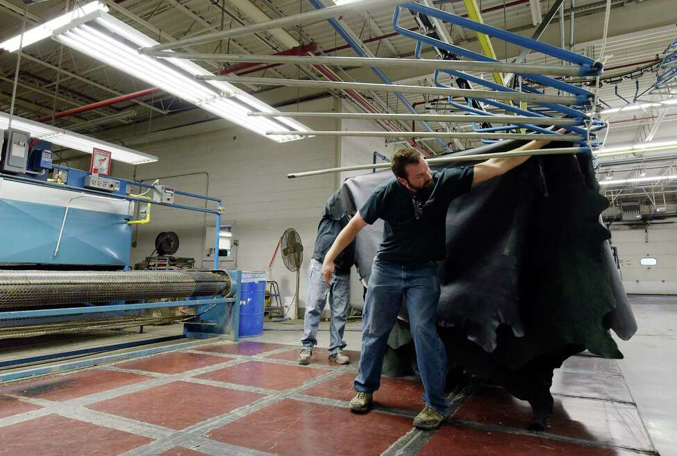 Employees, Kevin Kowalski, background left, and Jeremy LeBarron hang a large piece of leather after it comes off the finishing spray line at Townsend Leather on Monday, March 5, 2018, in Johnstown, N.Y. (Paul Buckowski/Times Union)