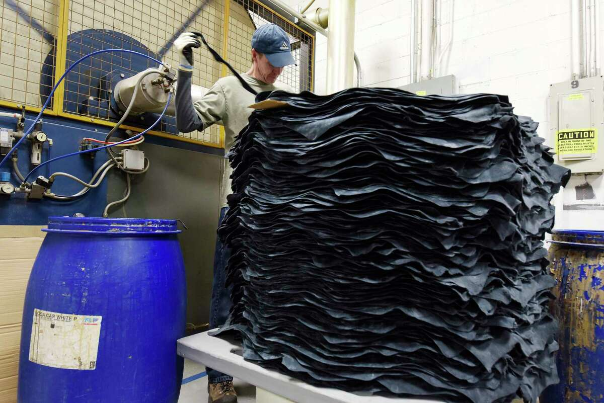 Employee Larry Skonieczny trims a stack of pigskins at Townsend Leather on Monday, March 5, 2018, in Johnstown, N.Y. (Paul Buckowski/Times Union)