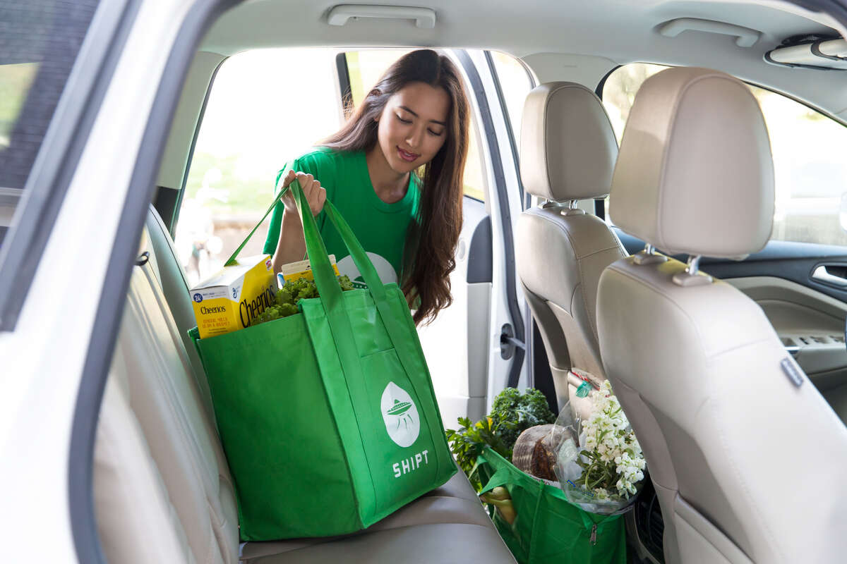 A Shipt shopper loads groceries in a car to be delivered.