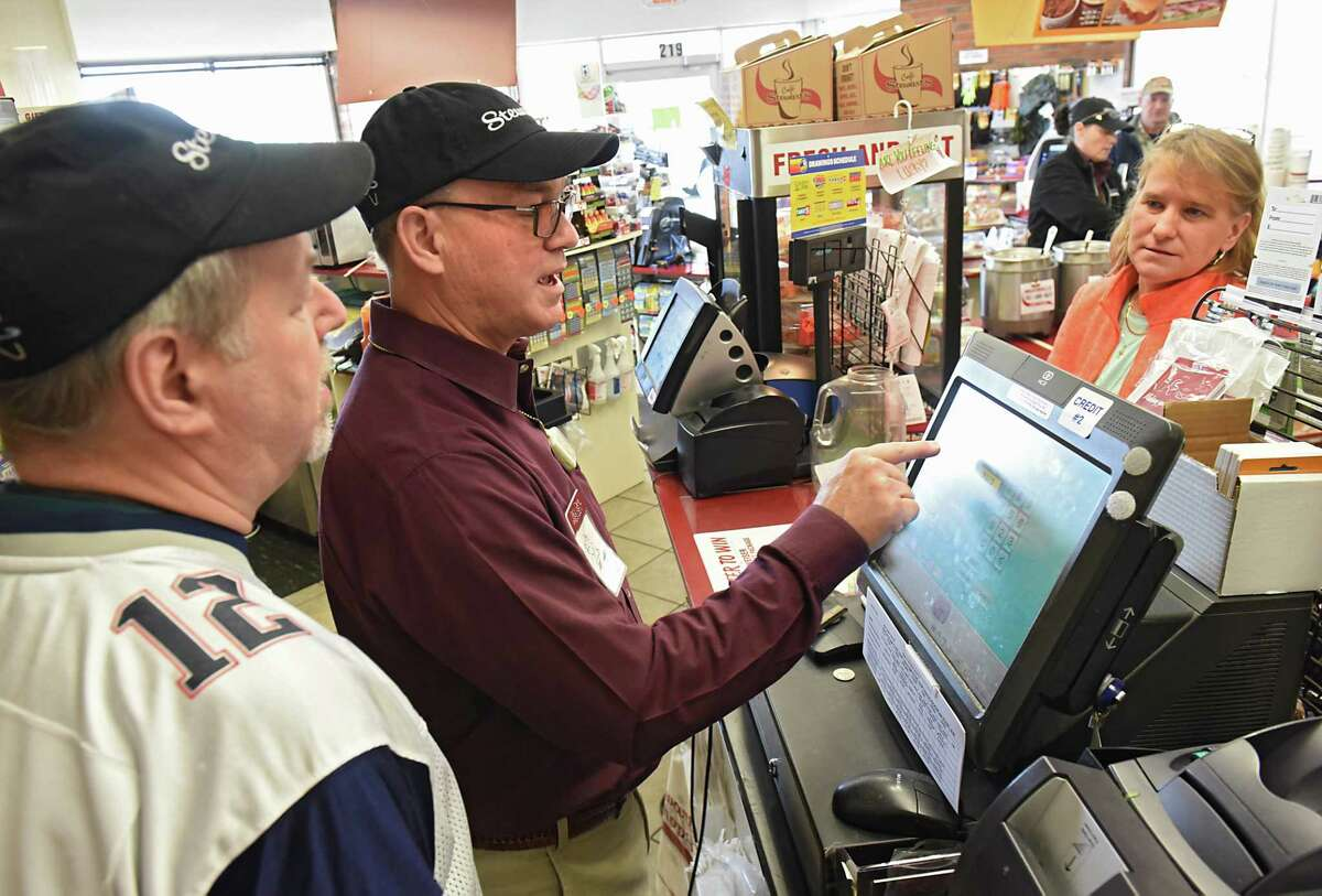 """StewartOs Shops President Gary Dake, center, continues a Holiday Match tradition by working a shift at the StewartOs Shop on Sand Creek Road on Friday, Feb. 3 2017 in Colonie, N.Y. The 2016 Holiday Match campaign received donations of more than $926,000 which becomes more than $1.85 million with the StewartOs match. Here Dake is helped by retired store manager Jay Letourneau, left, sell a lottery ticket to Molly Sherwin of Coloine, right, who used to manage Stewart's Shops in the area. She won the lottery and still continues to buy tickets because """"it's fun"""" she says. (Lori Van Buren / Times Union)"""