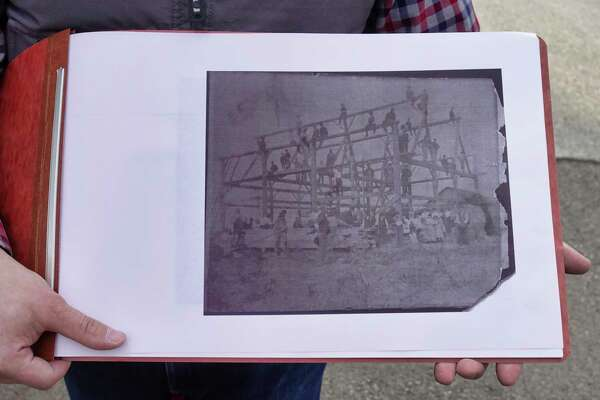 Billy Burns shows a copy of a photo from 1910 that shows a large being built on the former Shaker farm, on Sunday, April 7, 2019, in Loudonville, N.Y.   (Paul Buckowski/Times Union)