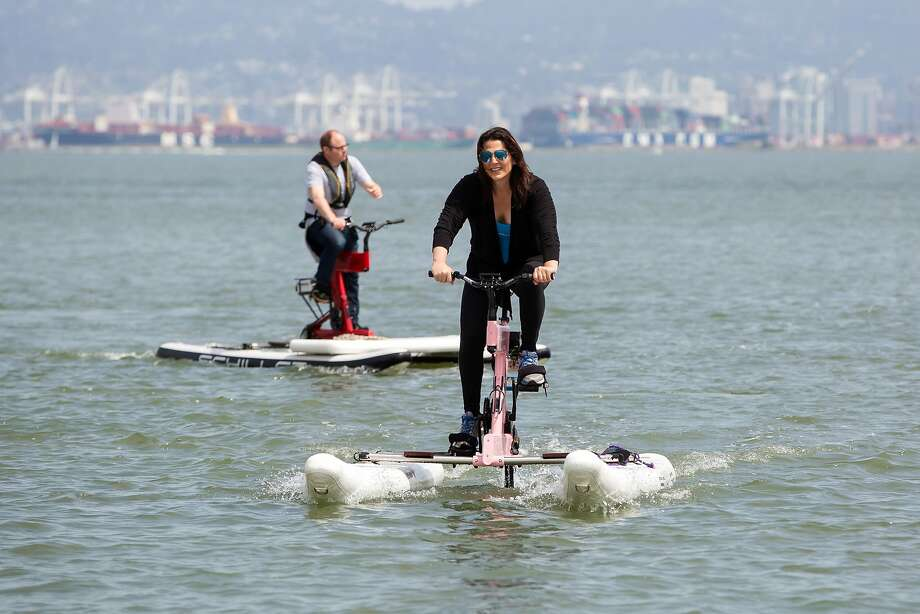 Electric-assisted water bikes navigate San Francisco's McCovey Cove, pedaled by Schiller Bikes founder Jessica Schiller (right) and Matthew Shambroom. Photo: Brittany Hosea-Small / Special To The Chronicle