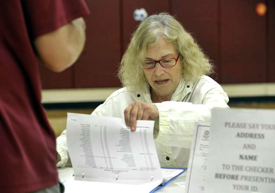 File photo from the May 10, 2018 budget referendum of Marietta Homayonpour checking names and addresses of voters at the Berry School polling place. Photo: Carol Kaliff / Hearst Connecticut Media / The News-Times