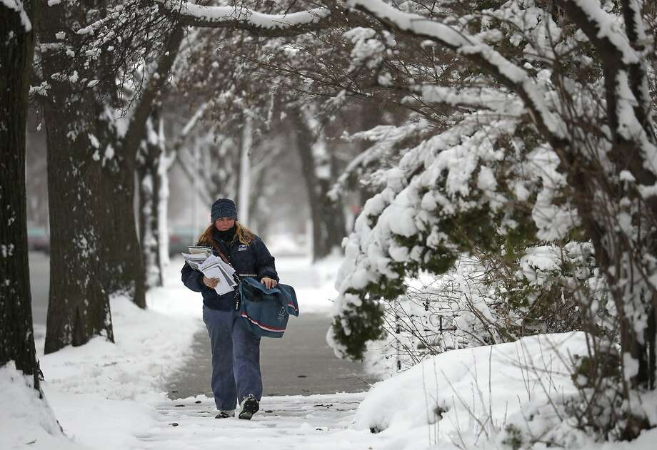 Postal worker Ginny Klein delivers mail in windy storm conditions after a spring blizzard hit Oshkosh, Wis. Photo: Dan Powers / Appleton (Wis.) Post Crescent
