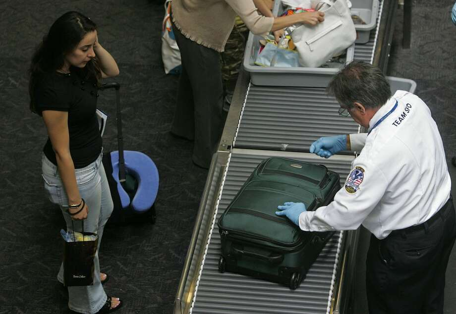 FILE - A TSA employee searches the luggage of a United Airlines passenger at a security checkpoint at San Francisco International Airport on Aug. 10, 2006. TSA officers are required to report any suspected violations of law, including possession of marijuana and cannabis infused products. While they don't search for marijuana or other illegal drugs, in the event they find an illegal substance, they will refer the matter to a police officer to enforce state law. Photo: Justin Sullivan/Getty Images