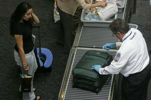 FILE - A TSA employee searches the luggage of a United Airlines passenger at a security checkpoint at San Francisco International Airport on Aug. 10, 2006. TSA officers are required to report any suspected violations of law, including possession of marijuana and cannabis infused products. While they don't search for marijuana or other illegal drugs, in the event they find an illegal substance, they will refer the matter to a police officer to enforce state law.