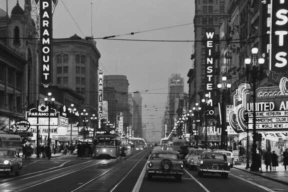 Street scene of cars and trolley traveling along Market Street by Paramount Theater, San Francisco, California, 1955.