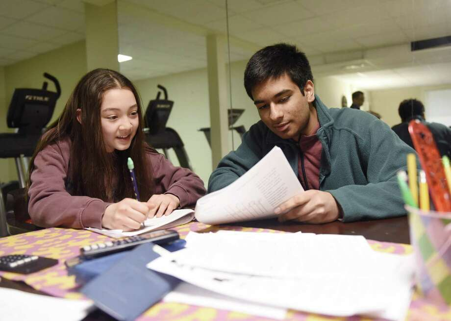GHS junior Nyle Garg and sixth-grader Lelle Sproule work out a math problem during a Sunday tutoring session at his home in Greenwich, Conn. Sunday, March 31, 2019. Garg runs a Sunday math tutoring academy out of his home with several other tutors who help younger students in small groups. Photo: Tyler Sizemore / Hearst Connecticut Media / Greenwich Time