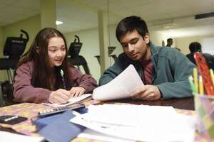 GHS junior Nyle Garg and sixth-grader Lelle Sproule work out a math problem during a Sunday tutoring session at his home in Greenwich, Conn. Sunday, March 31, 2019. Garg runs a Sunday math tutoring academy out of his home with several other tutors who help younger students in small groups.