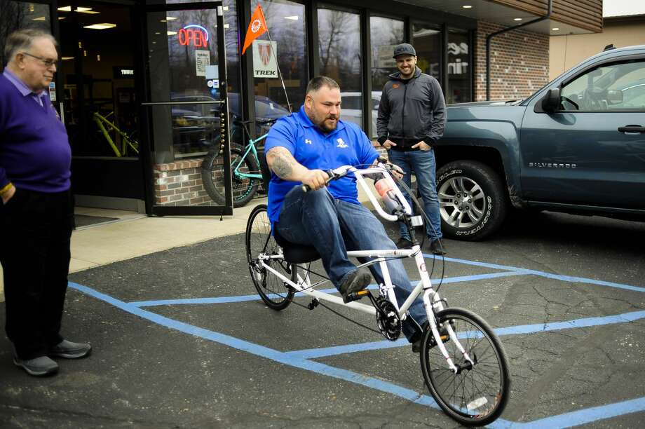 Adam Morton of Saginaw takes his brand new recumbent bike for spin around the parking lot on Wednesday, April 10, 2019 at Ray's Bike Shop in Midland. Morton is a veteran, and while serving in Iraq an explosion left him with debilitating injuries to his back and right leg, making it much too painful to use a regular bike. Morton received the bike through the Buddy to Buddy program, with a donation from The Fallen and Wounded Soldiers Fund. (Katy Kildee/kkildee@mdn.net) Photo: (Katy Kildee/kkildee@mdn.net)