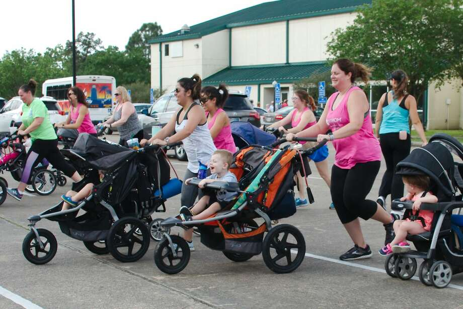 Moms and children take a jog during an activity at Stroller Strides class at Walter Hall Park Thursday, Apr 11. Photo: Kirk Sides/Staff Photographer