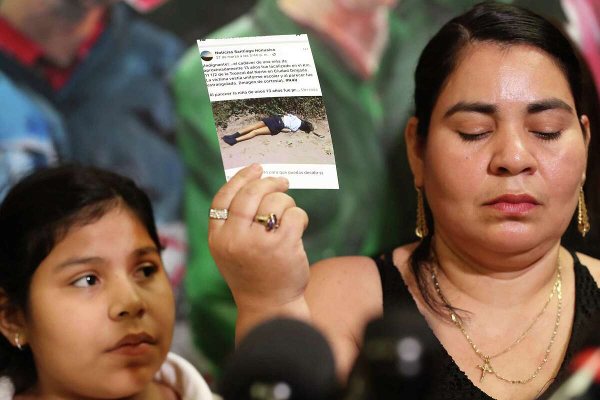 Doris Avardo (right) shows a photo of a friend of her family that was killed in El Salvador as her Laura Maradiaga,11, is facing deportation back Thursday, April 11, 2019, in Houston.