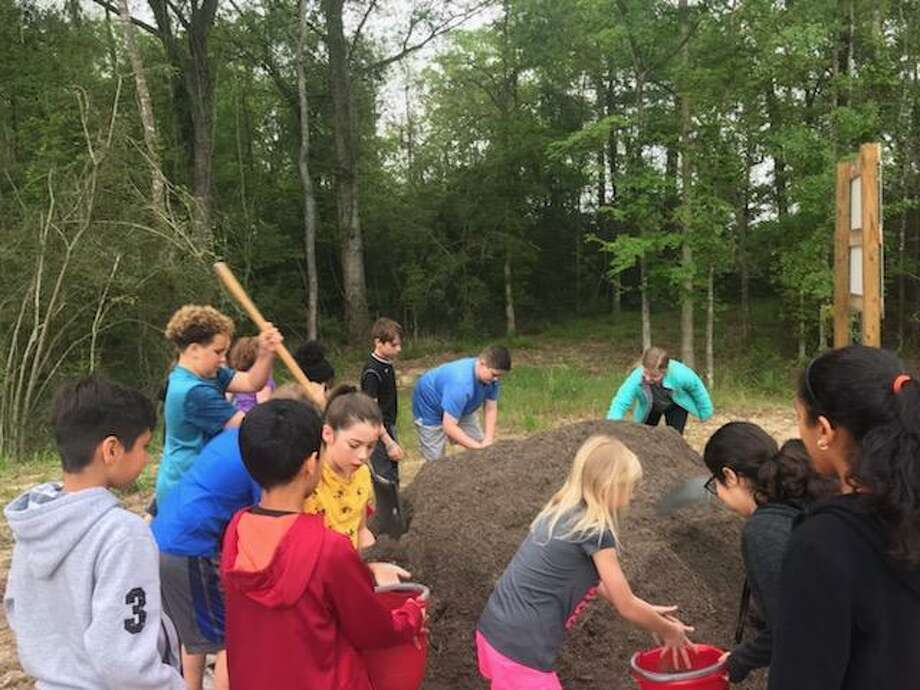 Students at Falcon Ridge ELementary School in Huffman work to help create the new garden at the school Photo: Andrea White