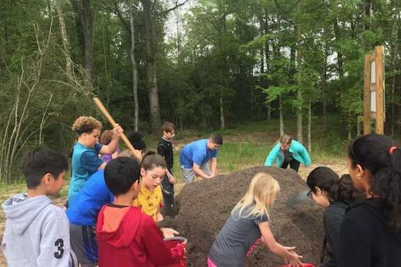 Students at Falcon Ridge ELementary School in Huffman work to help create the new garden at the school