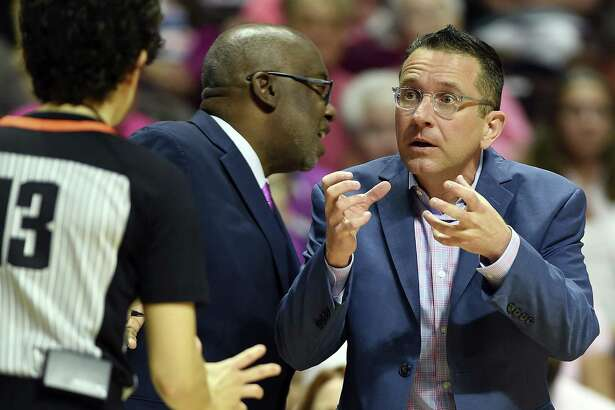 Connecticut Sun head coach Curt Miller, right, argues a call with official Cheryl Flores during the first half of a WNBA game action against the Las Vegas Aces on Aug. 5.