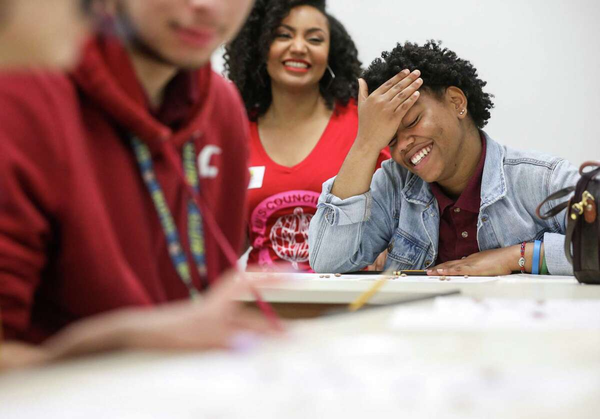 Eyanni Waterman, right, 17, laughs as she tries to balance a budget with the help of Stephanie Milburn, second from right, during exercise in a global business at Wisdom High School on Wednesday, April 10, 2019, in Houston. A group from the Houston Black Real Estate Association visited the class to help teach students about financial literacy.